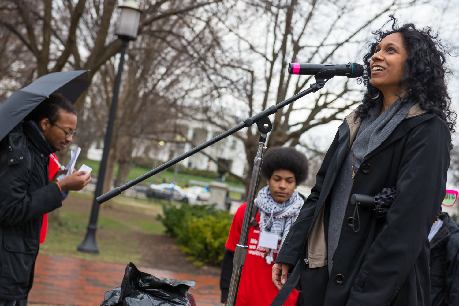 Image of Gowri Koneswaran standing behind a microphone in front of the White House. She wears a black trench coat and grey wool cowl neck sweater. She has a umbrella under her left arm with her hands by her sides and looks upwards with an inspired look.