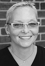 Black and white photo of Jan Beatty wearing rectangular light colored glasses. Her hair is cropped short. She is smiling pleasantly and wears small silver earrings, a chain necklace, and a black v-neck shirt.