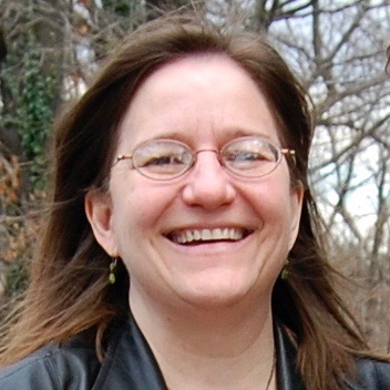 A white woman with brown hair and glasses smiles broadly with trees in the backgroun