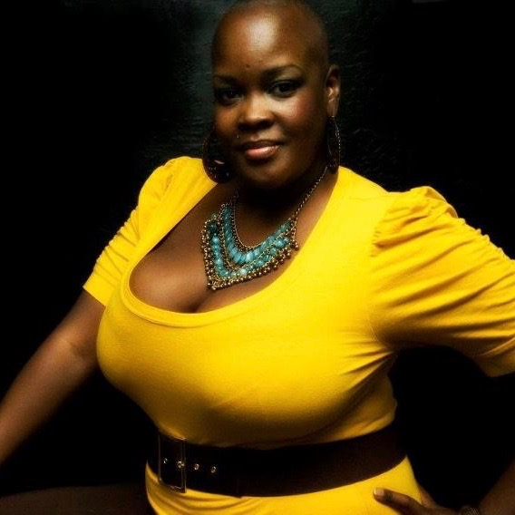 A black woman poses in a bright yellow shirt and turquoise necklace powerfully in front of a black background