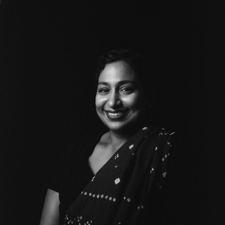 A smiling indian woman wearing traditional garb in a black and white photo
