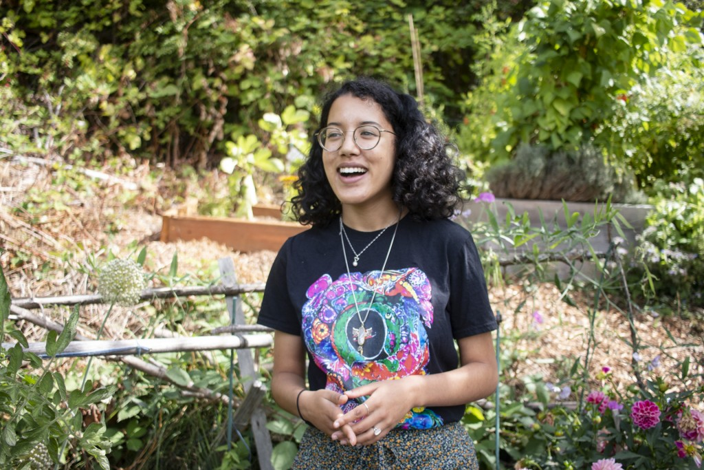 Azura Tyabji wearing glasses and a black t-shirt with a colorful design standing in front of a garden.