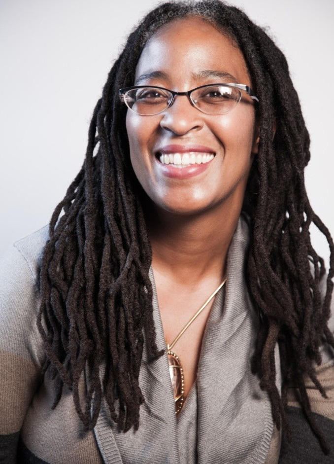 Portrait image of Camille Dungy smiling directly at the camera. She wears narrow, cat-eye glasses, a cardigan style sweater in multi-toned neutral colors of black, beige, and silver-gray. She wears a long, gold, necklace with large tawny colored stone pendant in a gold setting. Her dark hair is styled in long dreadlocks and parted in the middle.