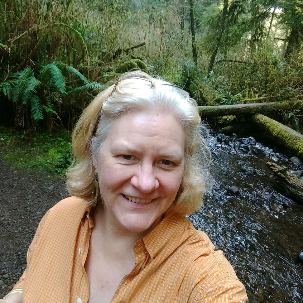 Sarah Browning appears outdoors while hiking. She wears an orange blouse and smiles toward the camera.