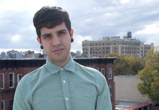 Image of Christopher Soto with fairly short dark hair, wearing a green stripped shirt buttoned all the way to the top, looking seriously towards the camera, and standing in front of a cityscape in the daytime.