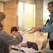 Image of a person receiving a program book at the registration table.