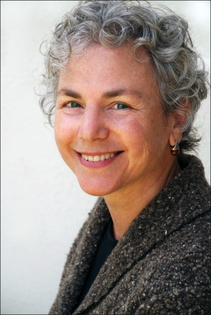 Image of Ellen Bass against a white background. Ellen has short, curly salt and pepper hair and green eyes. She wears a black shirt, grey wool jacket and silver earrings with a brown stone on the bottom. She is turned to the viewer's left but smiling directly towards the camera.