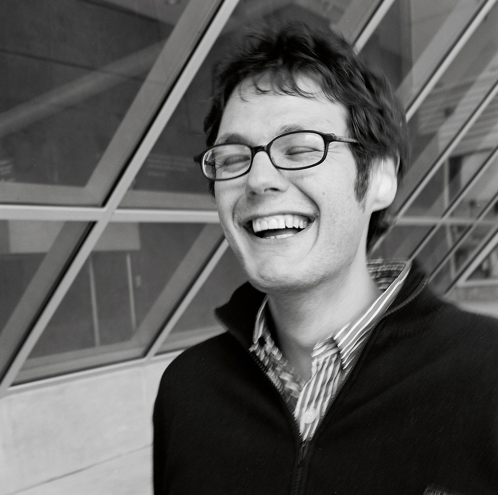Black and white image of Ilya Kaminsky with a broad smile and eyes closed in mid-laugh. He wears dark framed glasses and a striped button up shirt under a dark fleece jacket zipped up just below the collar of his shirt. He has dark fairly short hair with loose waves. To his right is a slanted wall of windows with white framing that reflects other buildings in the area.