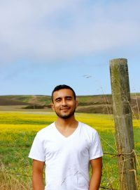 Image of Javier against a field of grass and yellow flowers. He wears a v-neck white t-shirt. His hands are to his side and he smiles while looking directly into the camera. Directly next to him is a wooden post from a fence. This portrait is taken from the waist up.