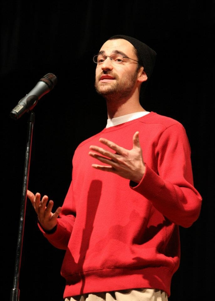 Photo of Jonathan Tucker at a microphone speaking. He is a white man wearing a red long sleeved shirt and glasses.