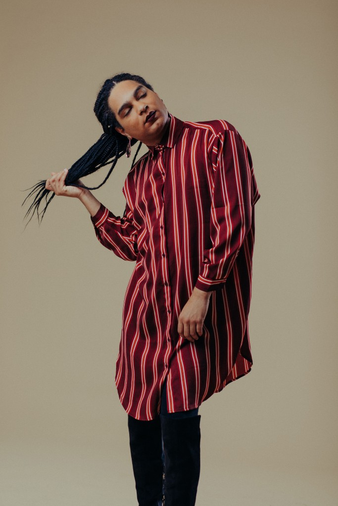 Justice Ameer in a red-striped shirt dress holding her braids with her eyes closed standing against a tan backdrop.