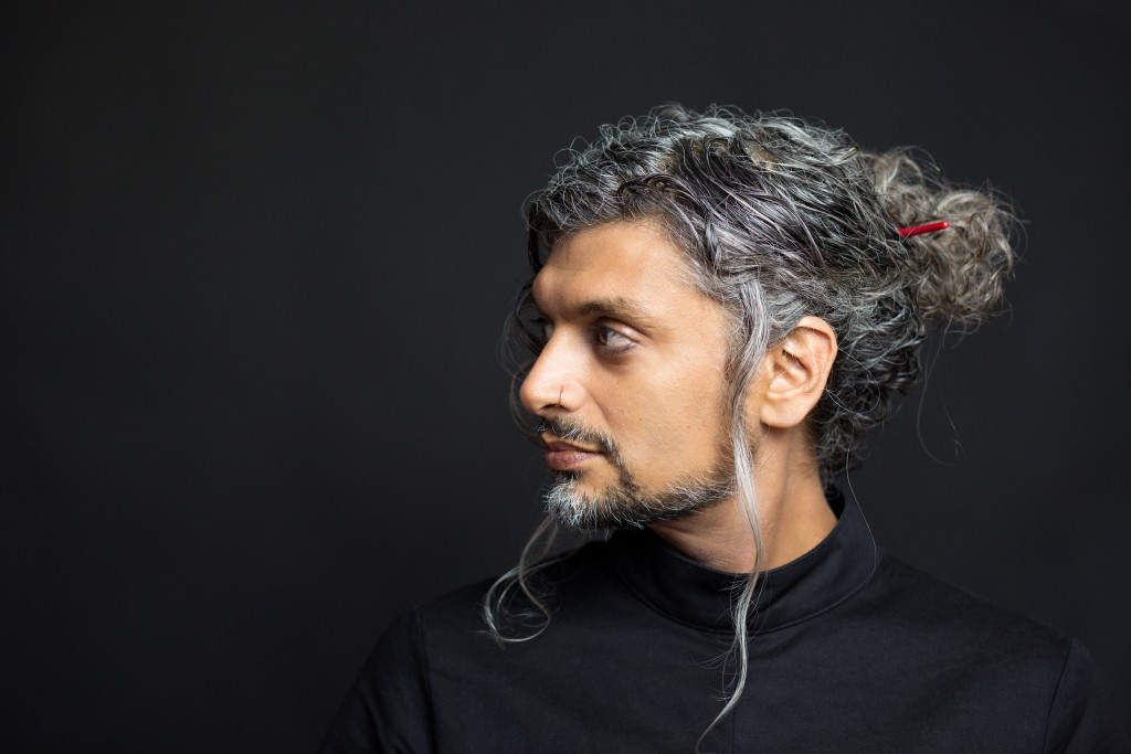 Image of Kazim Ali against a black background. Kazim wears a black turtleneck and looks slightly towards his right shoulder. He has a moustache, and a short goatee with side burns. His long, wavy salt and pepper hair is pulled back into a tousled bun held together with a red hair stick. His expression is neutral.
