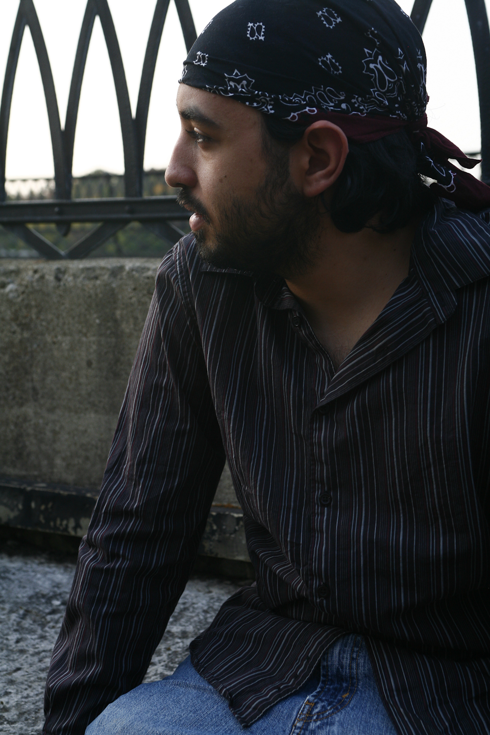 A man sits on a bridge above a river. In the background are trees, a bend in the river, railroad bridge. He is hunched a little forward with his hands resting on the bridge's concrete inner buttress. He is looking away from the viewer, down the length of the bridge, out of the shot. He has a dark, curly beard, and medium brown skin. His expression is contemplative, and as if he just about to speak. He is wearing a blue and white bandanna, a dark-colored shirt with multi-colored stripes, and blue jeans.