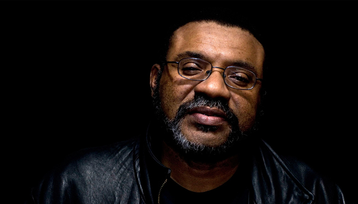 Image of Kwame against a black background. Kwame wears wire frame glasses and a leather jacket with a black shirt underneath. He looks directly into the camera, though his eyes are not fully open. He has a dark beard and mustache that is slightly graying. The portrait is taken from the shoulders up.