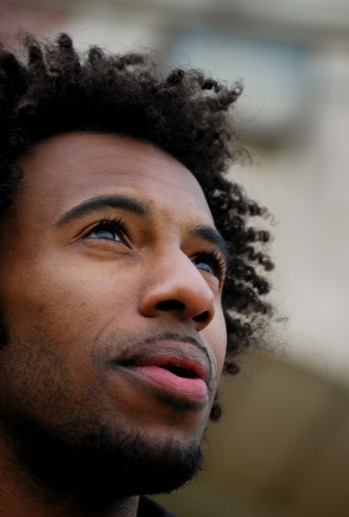 Profile photo of Kyle Dargan (a brown-skinned Black-American man with curly afro) looking up at the sky
