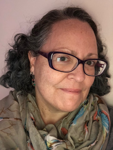 Portrait image of M. Soledad Caballero. She wears dark-framed glasses, a beige scarf with a floral pattern, and drop earrings with multicolored beads. She has dark hair with shocks of gray at her temples, and light brown eyes.
