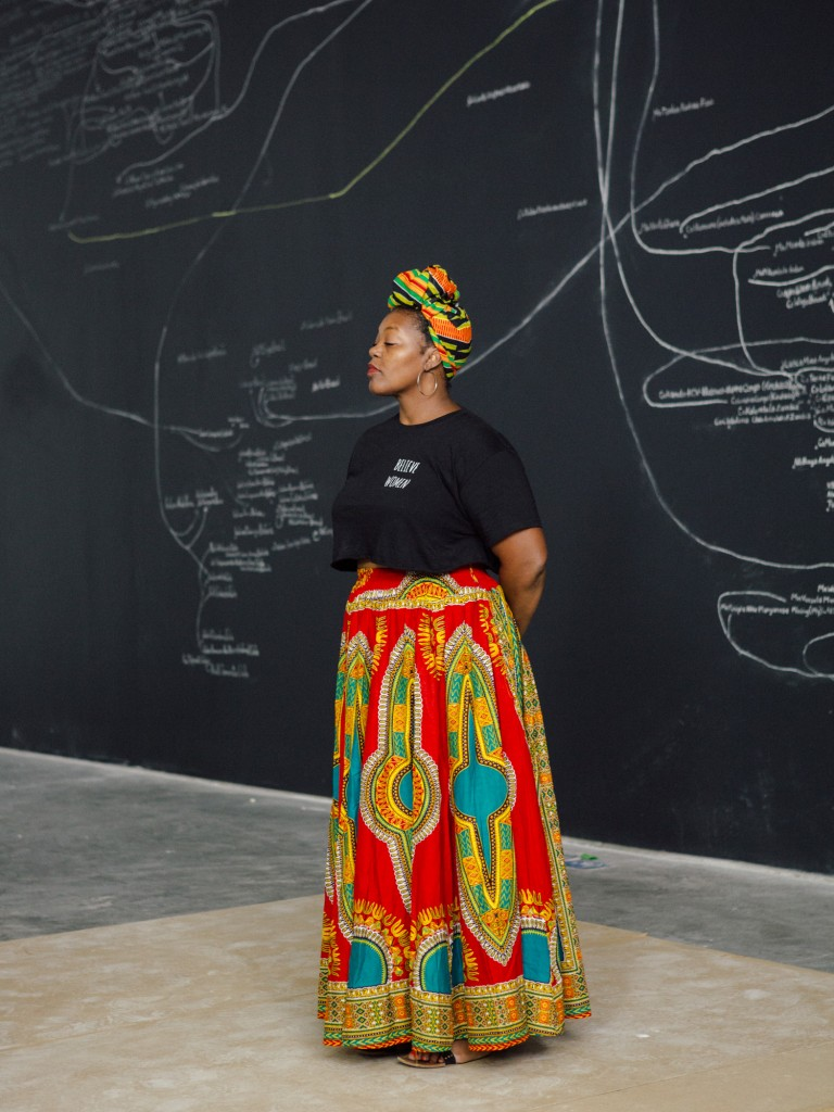 Mahogany L. Browne wearing a black shirt and colorful skirt standing in front of a chalkboard.