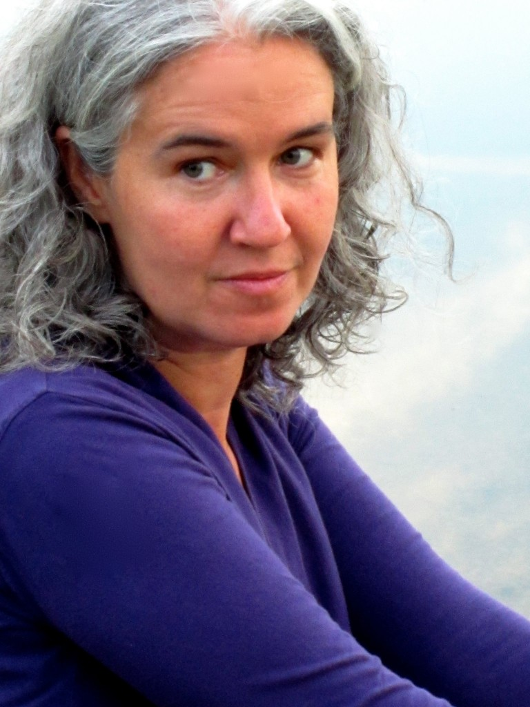 Photo of Melissa Tuckey wearing a purple long sleeve shirt. She is seated turned to the left and looks toward the camera over her right shoulder. Her gray wavy hair is slightly parted in the middle tucked behind her right ear. Her expression is neutral.