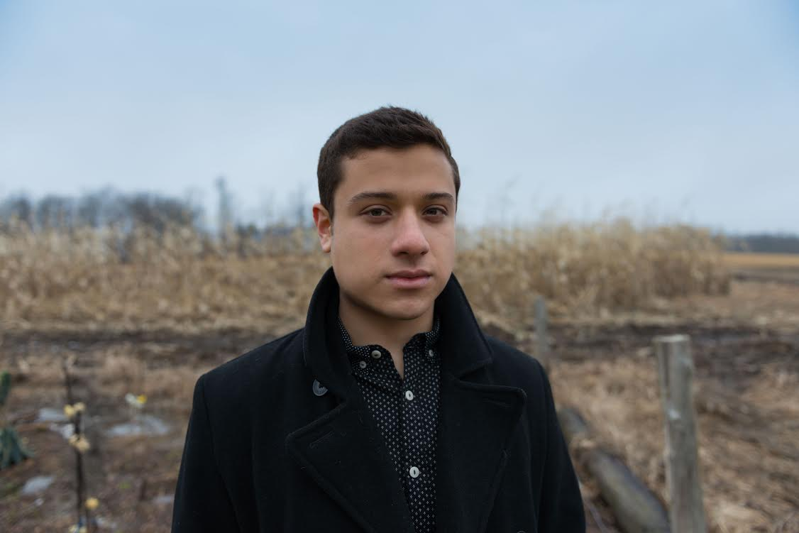 Image of Jonathan Mendoza standing near a winter corn field. The sky is blue and overcast. He looks directly at the camera, wears a heavy brown overcoat, and has short dark brown hair and brown eyes.