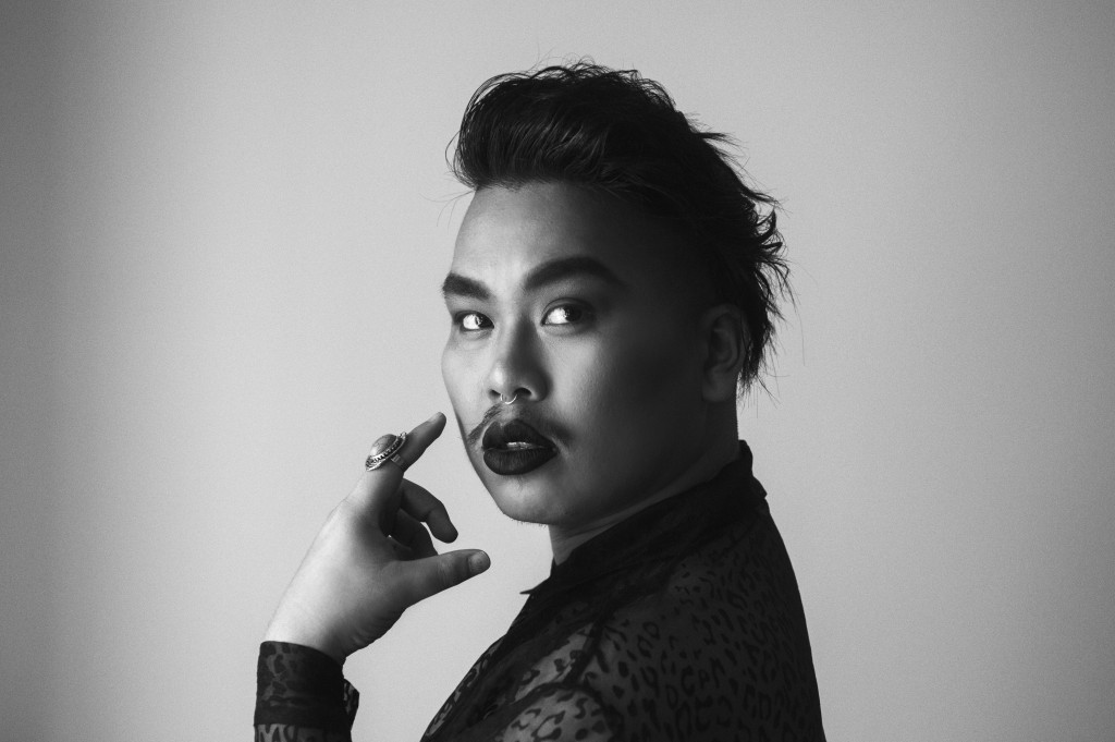 Black and white, portrait image of Paul Tran. They look over their left should directly at the camera with a serious expression. They wear a see-through, leopard print, button down shirt and a large silver ring on one hand with a stone that might be turquoise. Tran's dark hair is swept back in a tousled pompadour, and they are wearing a septum ring, dark lip stick, and a light mustache.