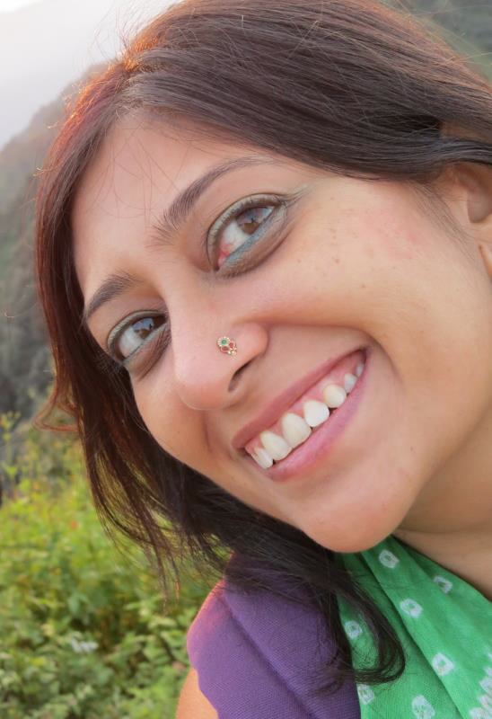 A close-up of a woman's face. Behind her is a large, forested hill or mountain. She has light chestnut hair, caramel colored eyes, and light brown skin. She is looking up and away to the right from the viewer, and she is smiling happily. She is wearing bright blue eyeliner, a green scarf with white polka dots, and the strap of a purple backpack just shows hanging on her left shoulder.