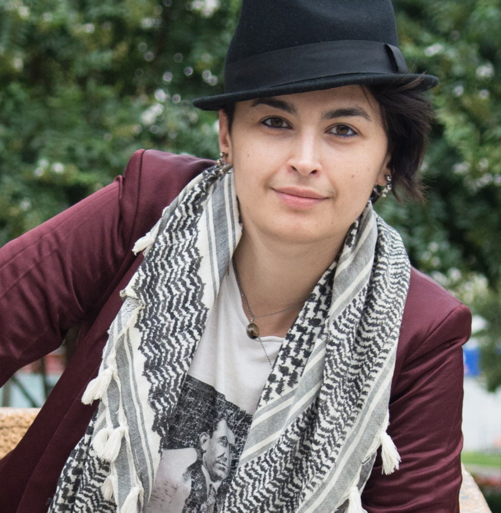 Rasha Abdulhadi appears outdoors, leaning forward with their elbow on their knee, with a neutral expression. They wear a black hat, maroon blazer, white graphic t-shirt, and patterned black and white scarf.