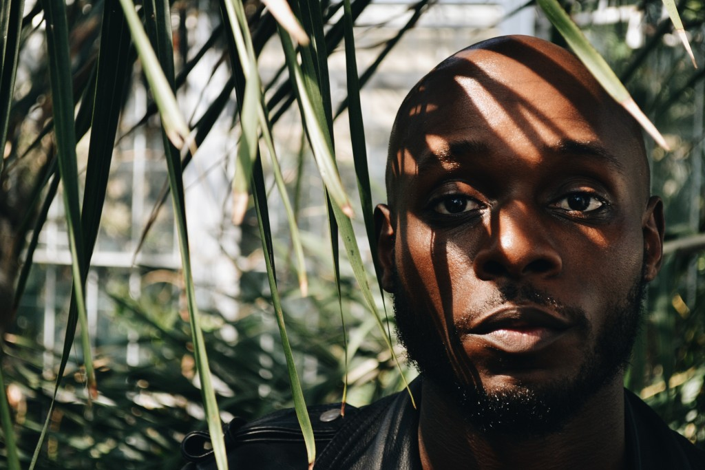 Image of Rasheed Copeland standing amongst thin palm leaves. He has a neutral expression and the shadow of the leaves appear across his face.