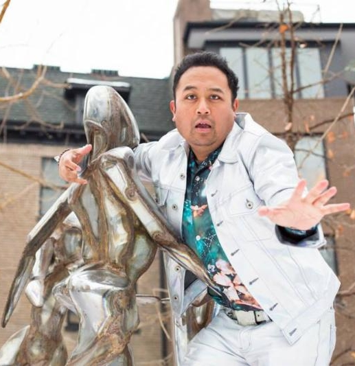 Photo of Regie Cabico in white jacket with arm around a sculpture