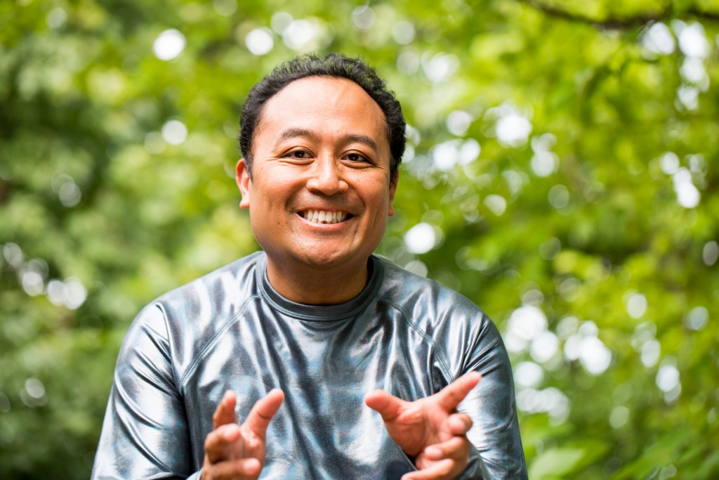 Regie Cabico appears outdoors with greenery in the background. He wears a silver shirt and smiles as he gestures with both hands toward the viewer.
