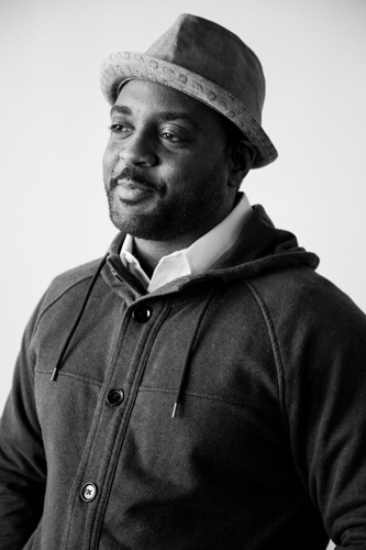 Black and white photo of Reginald Dwayne Betts in hat and a jacket with a slight smile