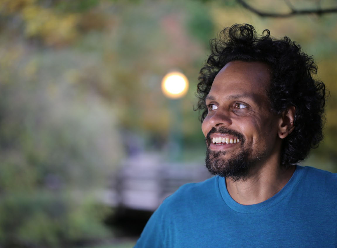 Photo of Ross Gay outside in blue shirt smiling