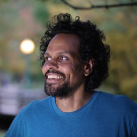 Image of Ross Gay. He wears a blue shirt and smiles. Blurred in the background are trees and a light post.