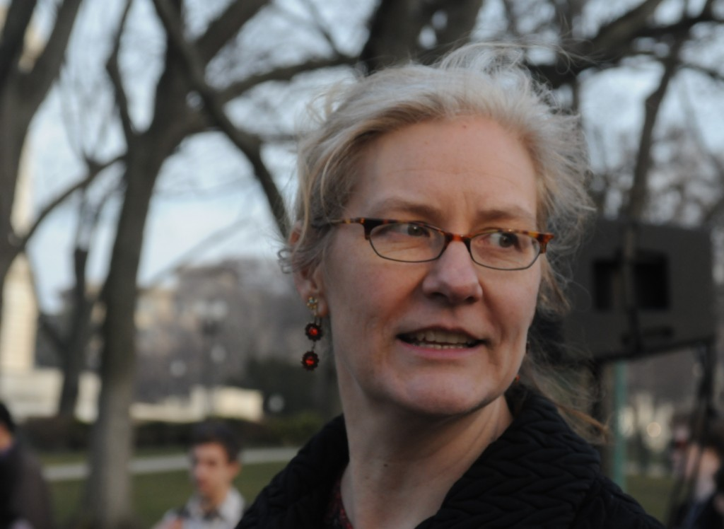 Sarah Browning appears outdoors with bare trees in the background. She wears a black sweater, glasses, and red earrings. She looks away from the camera.