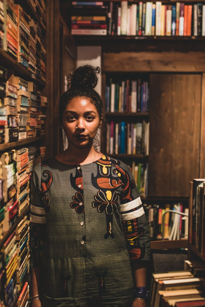 Safia Elhillo front facing looking into camera next to a shelf full of books.