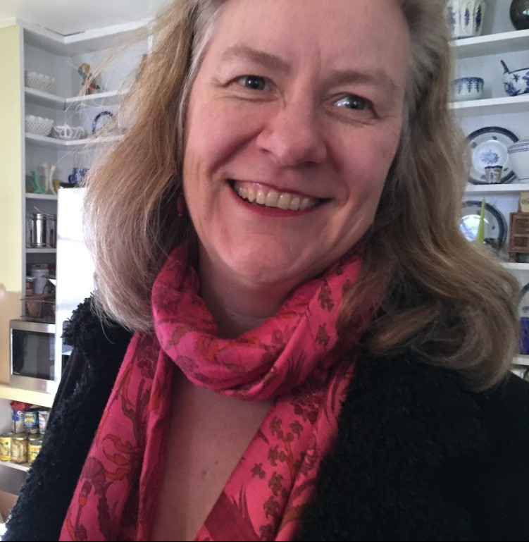 Sarah Browning, a white woman, stands and smiles. Her head is tilted slightly and she is looking into the distance. She wears a black coat and a pink scarf. In the background are shelves with plates and books.