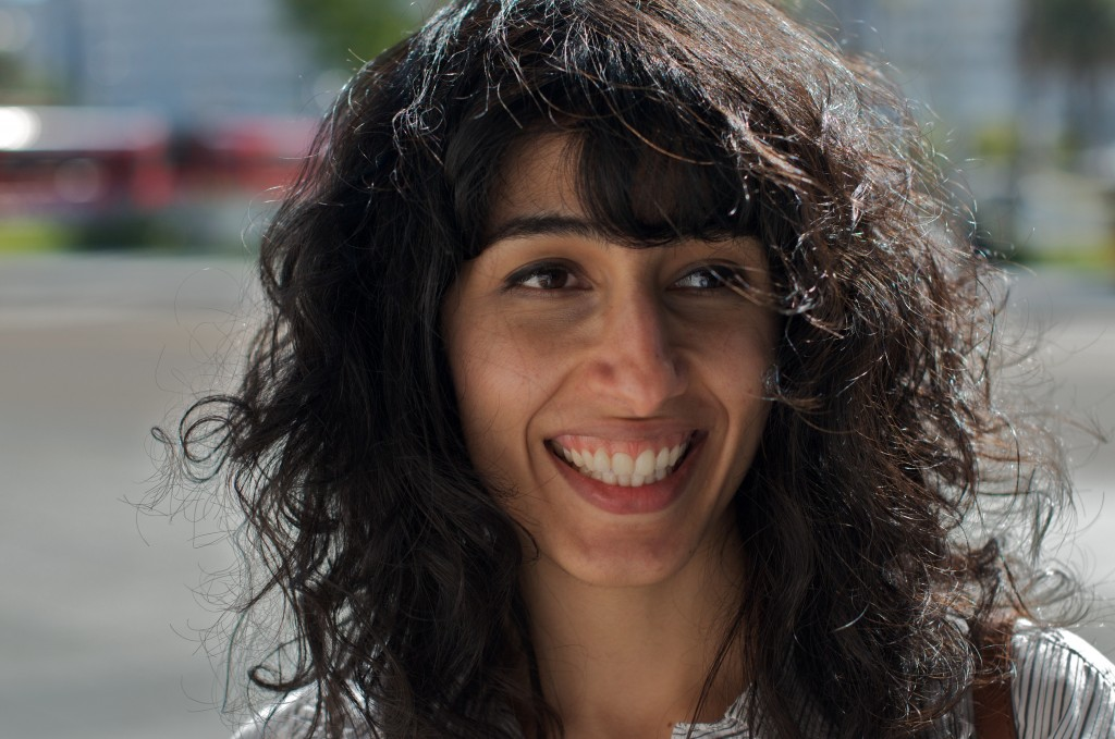 Image of Solomaz against a blurred urban background. Solomaz looks away from the camera, smiling. Her dark brown hair is styled in loose curls with bangs. She is wearing a white top. The portrait is taken from the shoulders up.