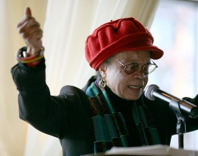 Photo of Sonia Sanchez. An African American woman in a red cap and glasses, standing at a podium speaking with her arms posed upward
