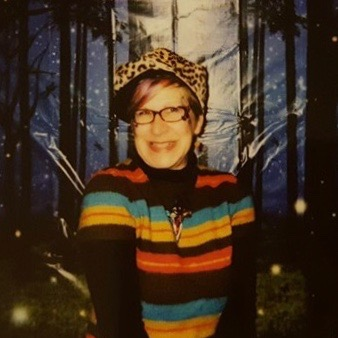 A white woman with short blond hair and glasses, wearing a rainbow shirt and leopard print hat smiles into the camera. She is in front of a forest background.