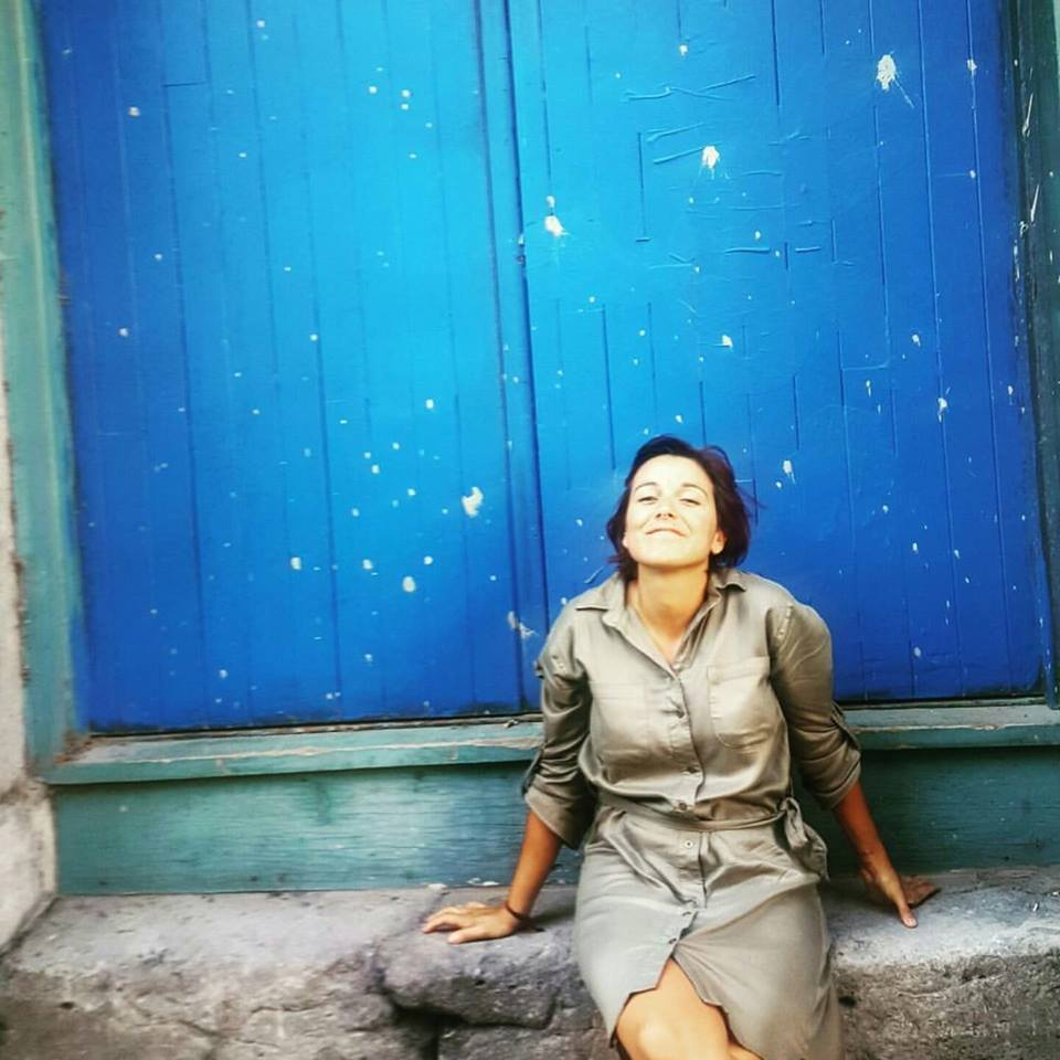 Image of Sylvia Beato wearing a tan button up dress sitting on a stone step in front of a blue wall. Sylvia's face is skyward and looks hopeful.