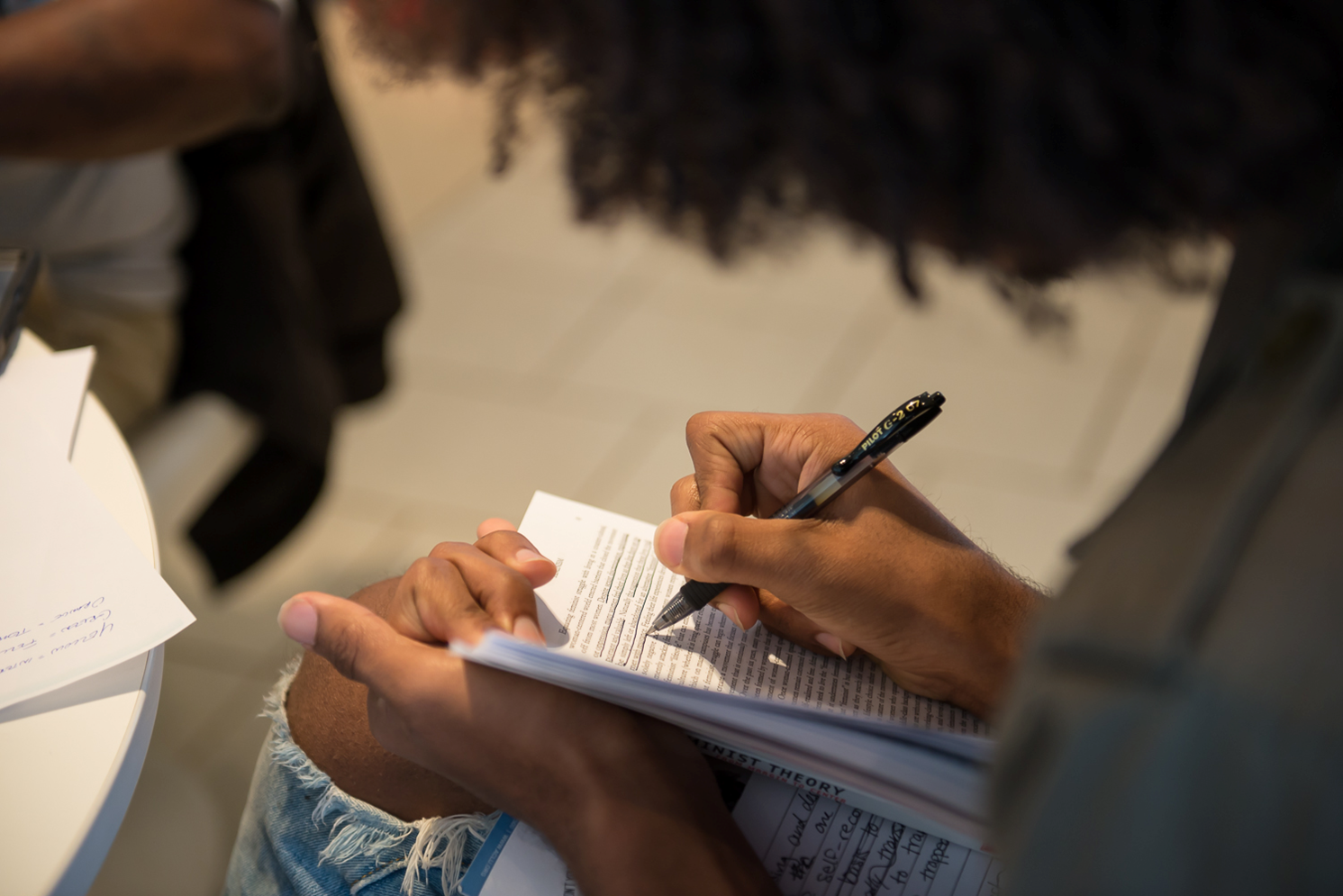 Close up photo of an individual sitting and writing in a notebook.
