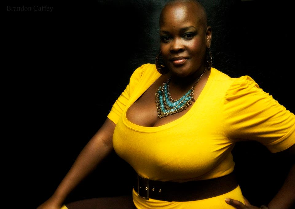 Image of Sonya Renee Taylor facing forward, wearing yellow short sleeved shirt with tourquoise necklace