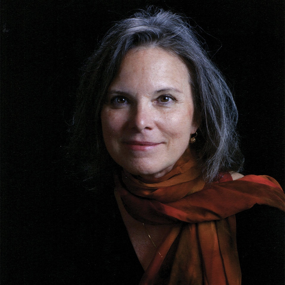 Color portrait of Carolyn Forché. She is a white woman with medium length, short hair and is wearing a dark scarf. She is smiling at the camera.
