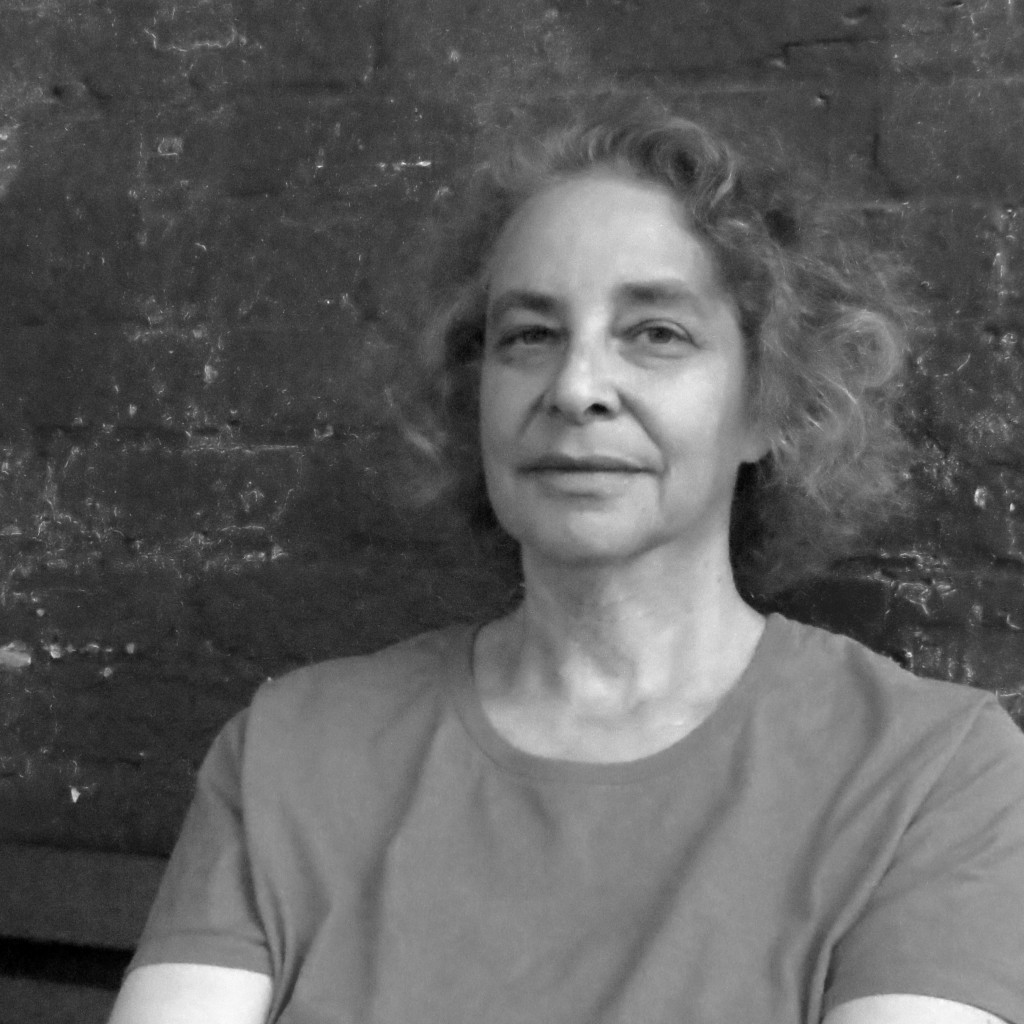 Black and white portrait of Kim Roberts. She is a white woman with curly, short hair. She is facing the camera and is wearing a light colored, short sleeved shirt.