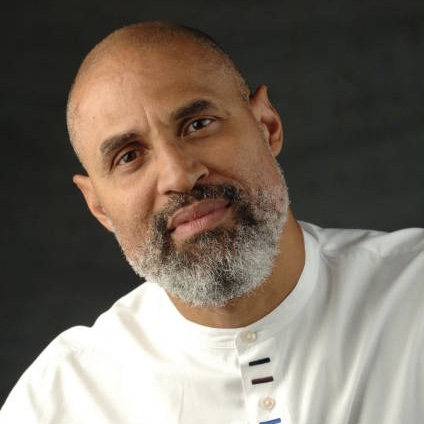 Color portrait of Tim Seibles. He is an African American man with a light colored beard and is wearing a light colored shirt. His head is tilted to the left and he is smiling at the camera.