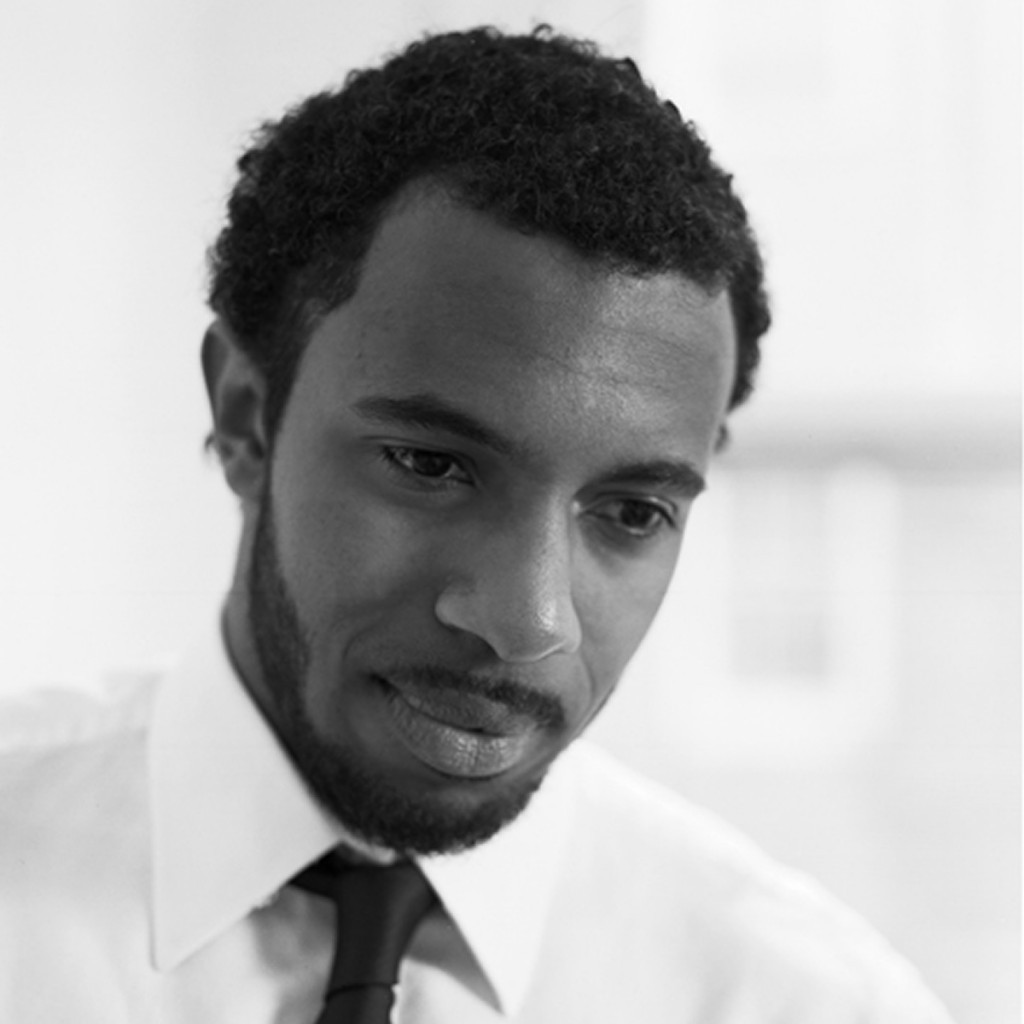 Black and white portrait of Kyle Dargan. He is an African American man with short, dark hair and a short beard. He is looking down and is smiling.