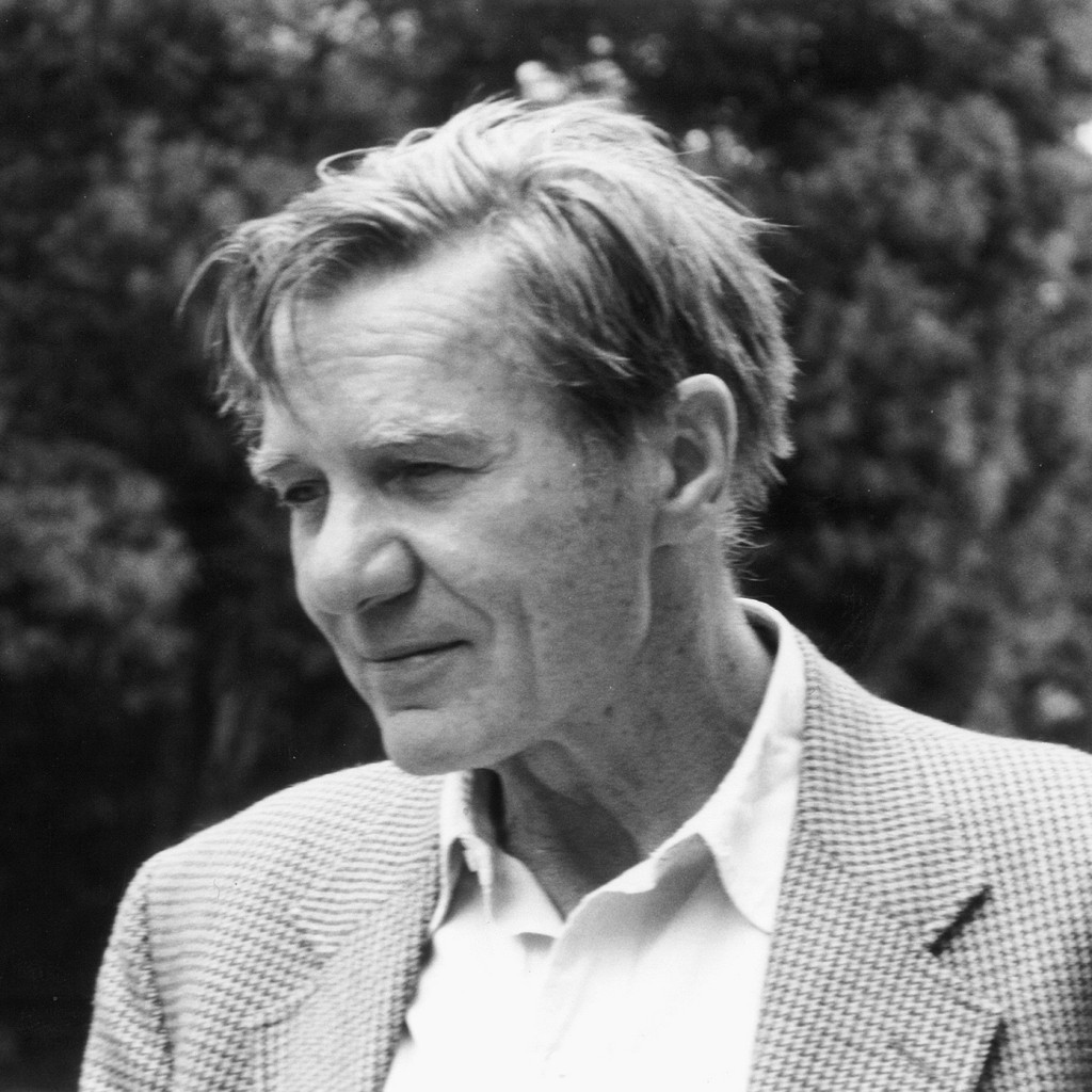 Black and white photo of Galway Kinnell. He is a white man with short, light colored hair and is at an angle to the camera. He is wearing tweed and a light colored button up.