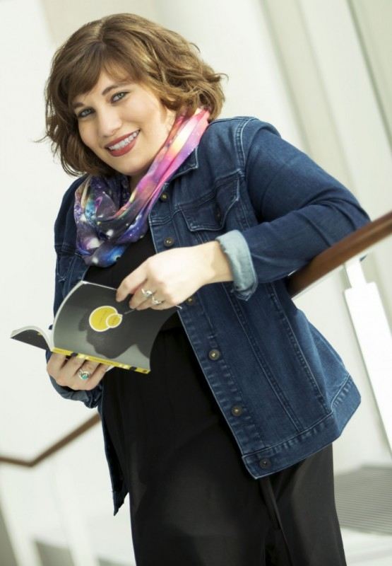 Marlena Chertock appears in front of a white background and leans against a wooden railing. She smiles while looking toward the camera and holds an open book. She wears a black dress, denim jacket, and multicolored infinity scarf.