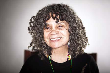 Portrait style image of Sonia Sanchez wearing a dark brown, heavily textured sweater, a necklace of multicolored beads, and drop earrings of a light colored stone. She smiles at the camera. She has warm brown eyes, and wears her salt-and-pepper hair in shoulder-length, curly, dreadlocks.